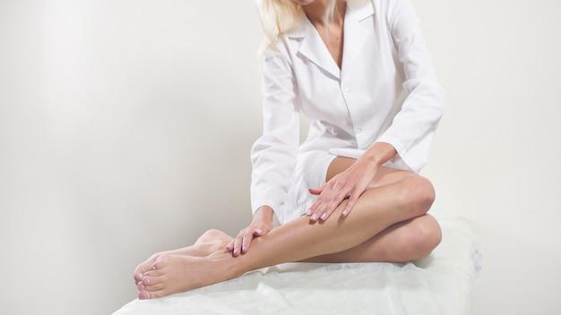Mulher toca suas pernas longas sexy. conceito de cuidados com o corpo