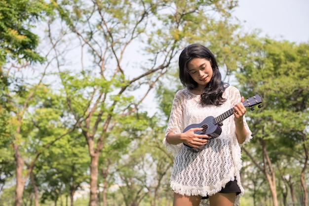 Mulher toca ukulele no jardim