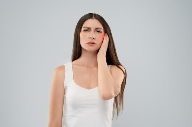Mulher tocando a cabeça por causa de dor de ouvido