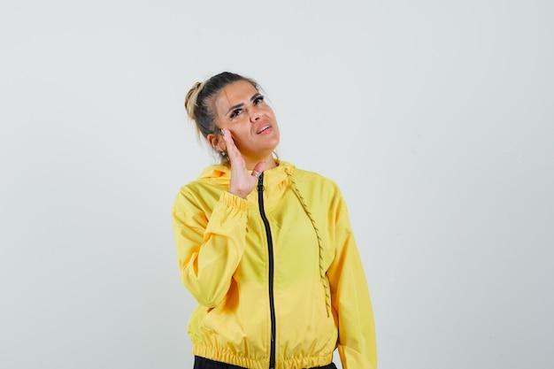 Mulher tocando a pele do rosto na bochecha em traje esporte e olhando pensativa, vista frontal.