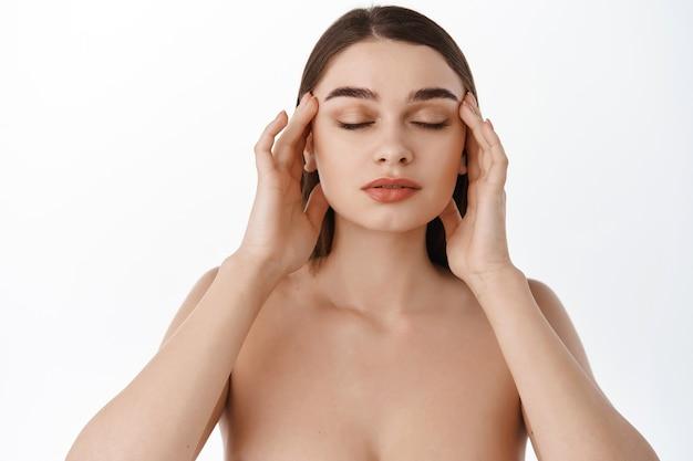 Mulher tocando as têmporas, dedos no rosto saudável e limpo, olhos fechados, massagem facial com óleo de argan, cosméticos para a pele, aplicação de creme, parede branca