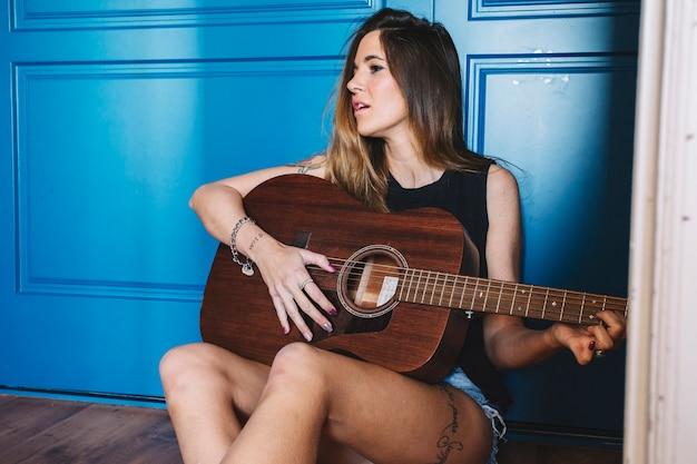 Mulher tocando guitarra perto da parede azul