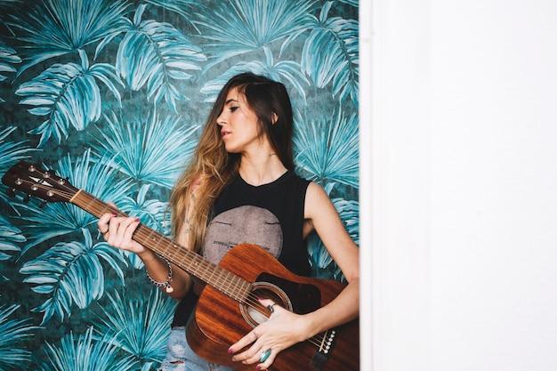 Mulher tocando guitarra perto da parede