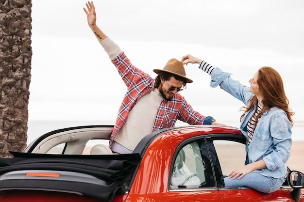 Mulher tocando o chapéu na cabeça do homem e inclinando-se para fora do carro