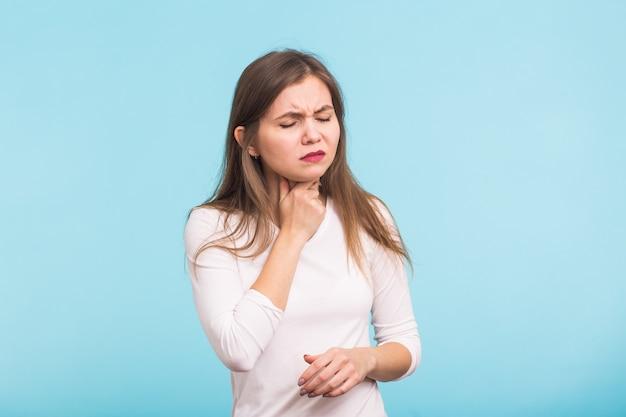 Mulher tocando o pescoço na parede azul
