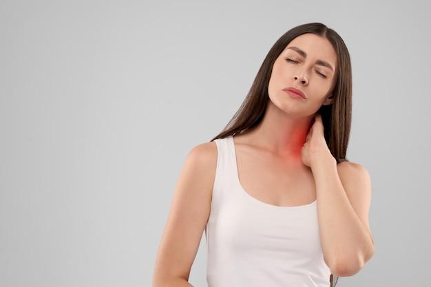 Mulher tocando o pescoço por causa da dor
