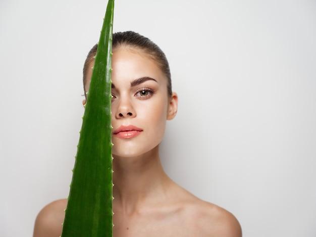 Mulher tocando o rosto com folha de babosa em fundo claro closeup retrato