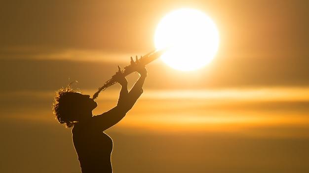 Mulher tocando saxofone no sol