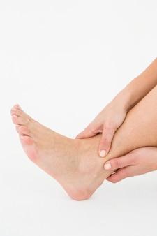 Mulher tocando seu tornozelo doloroso