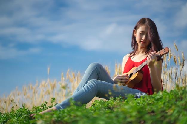 Mulher tocando ukulele no jardim.