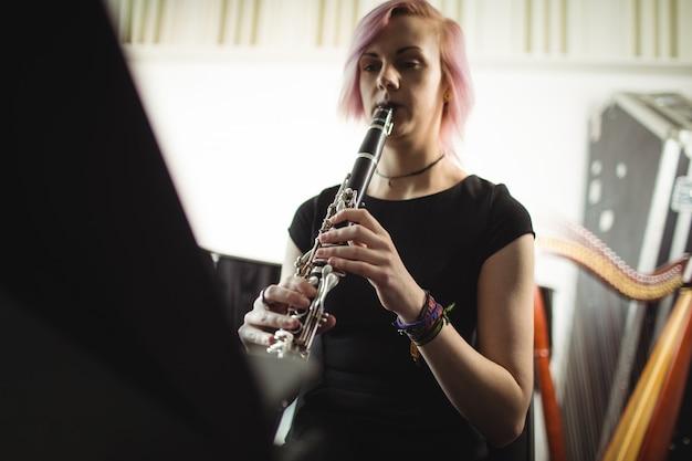 Mulher tocando um clarinete na escola de música
