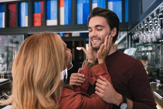 Mulher tocando um homem alegre e satisfeito que pegava as mãos dela
