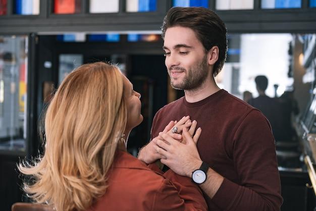Mulher tocando um homem bonito e satisfeito que fecha os olhos