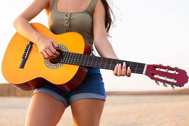 Mulher tocando violão ao ar livre na natureza