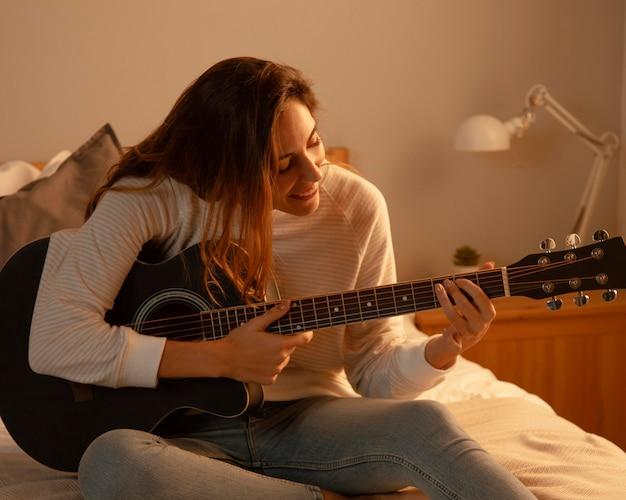 Mulher tocando violão em casa na cama
