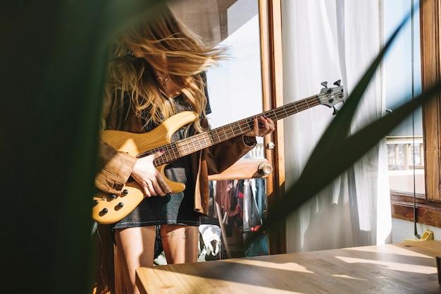 Mulher tocando violão na sala luz Foto gratuita