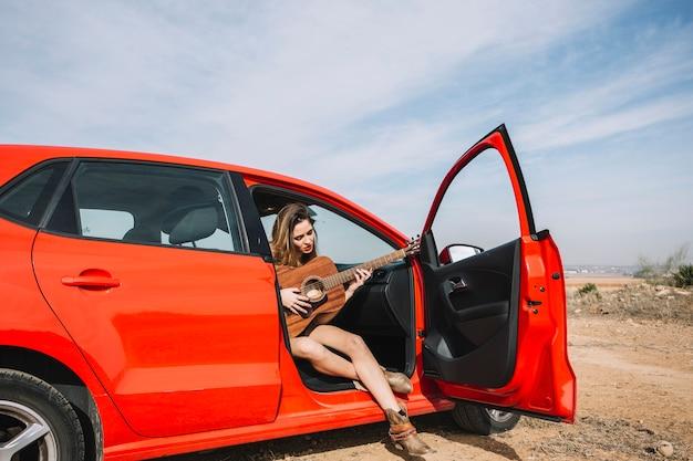 Mulher tocando violão no carro