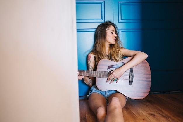 Mulher tocando violão no corredor