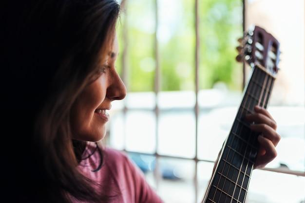 Mulher tocando violão para os vizinhos pela janela