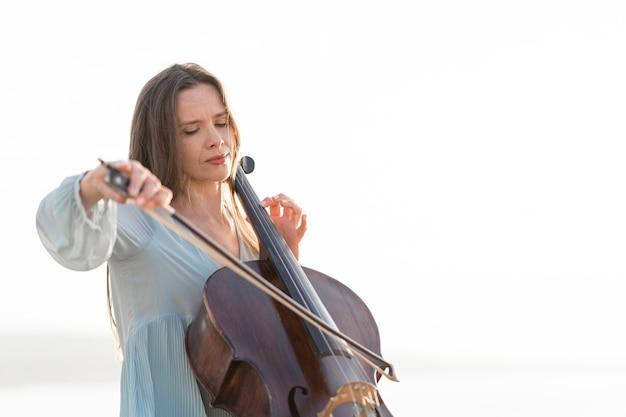 Mulher tocando violoncelo com espaço de cópia