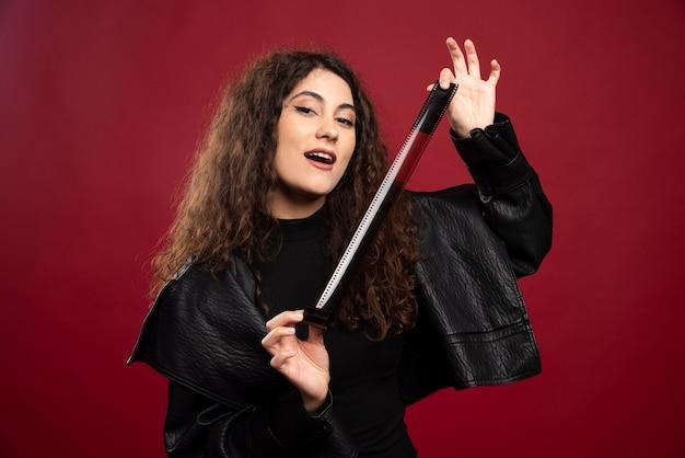 Mulher toda vestida de preto, mostrando uma fita fotográfica.
