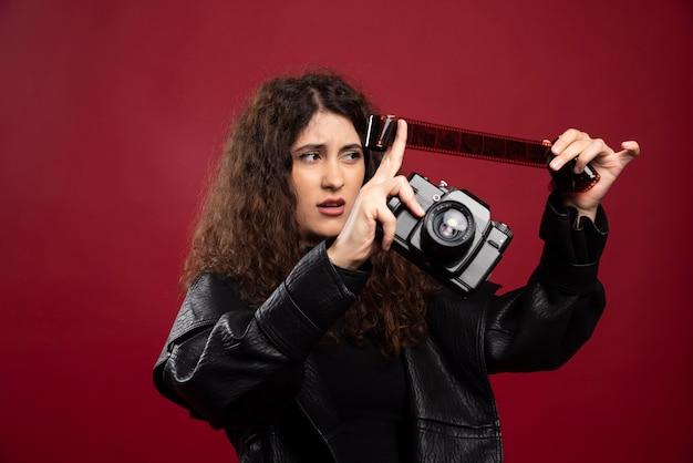 Mulher toda vestida de preto, segurando uma fita fotográfica com uma câmera.
