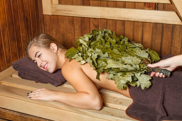 Mulher toma banho de vapor em uma sauna.