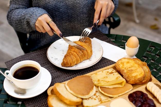 Mulher toma café da manhã com croissant e café