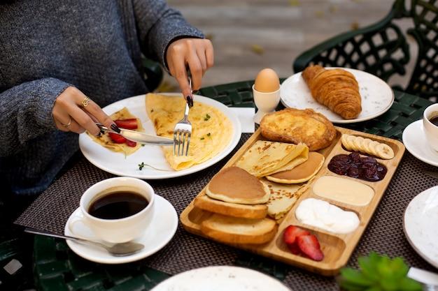 Mulher toma café da manhã com omelete e crepe