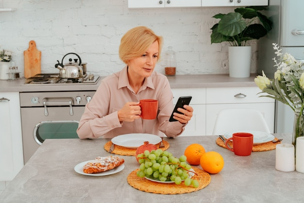 Mulher toma café da manhã em casa com frutas, bolo e café