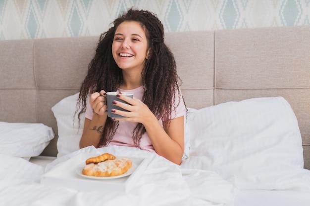 Mulher toma café da manhã na cama em um apartamento de hotel leve ou em casa. jovem retrato de luz de janela comendo croissant, bebendo café e sorrindo.