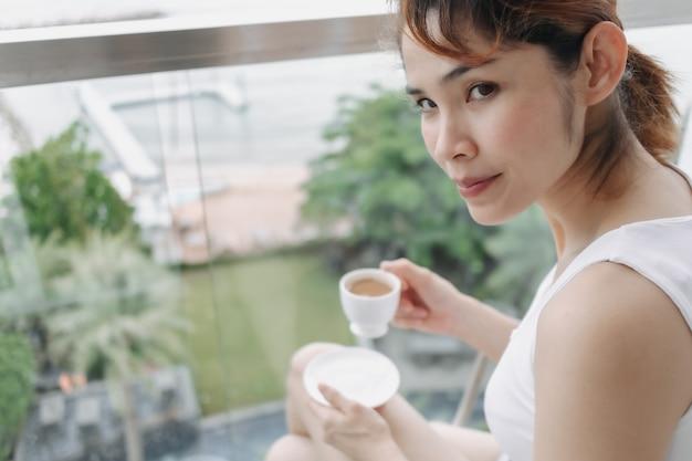 Mulher toma café e relaxa na varanda com vista para o mar