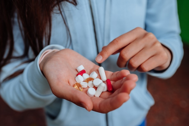 Mulher toma e mostra pílulas.