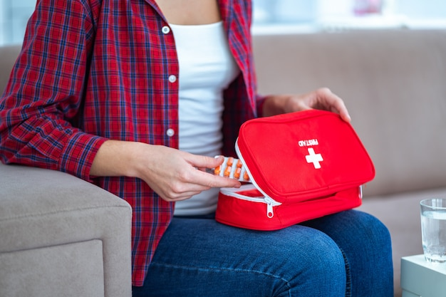 Mulher toma remédio de dor e doença em casa. kit médico de primeiros socorros