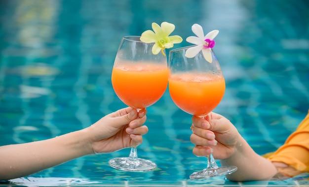 Mulher toma um copo de coquetel de suco de laranja com um amigo na piscina. férias de verão e relaxe sozinho em casa.