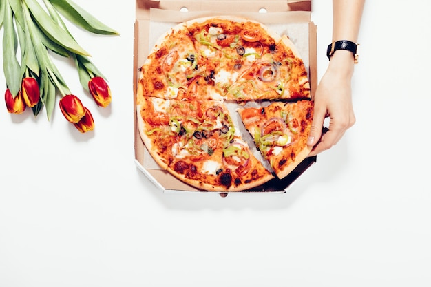 Mulher toma uma fatia de pizza da mesa