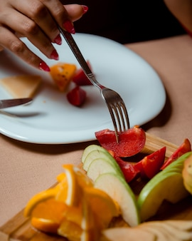 Mulher tomando ameixa com carne de porco do prato de frutas com maçãs, laranjas, bananas