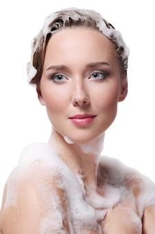 Mulher tomando banho com sabão no corpo e na cabeça. conceito de higiene e cuidados com a pele