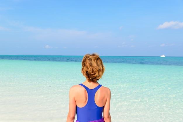 Mulher tomando banho de sol na água transparente turquesa, praia de areia branca, vista traseira, dia de sol, pessoas reais