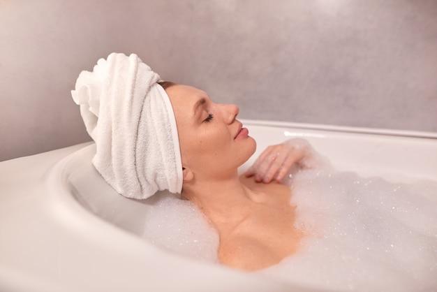 Mulher tomando banho de spa em casa e relaxando em uma banheira cheia de espuma