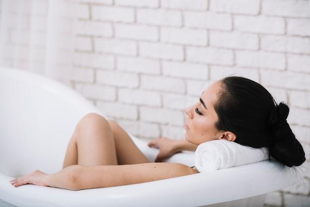 Mulher tomando banho relaxante em um spa