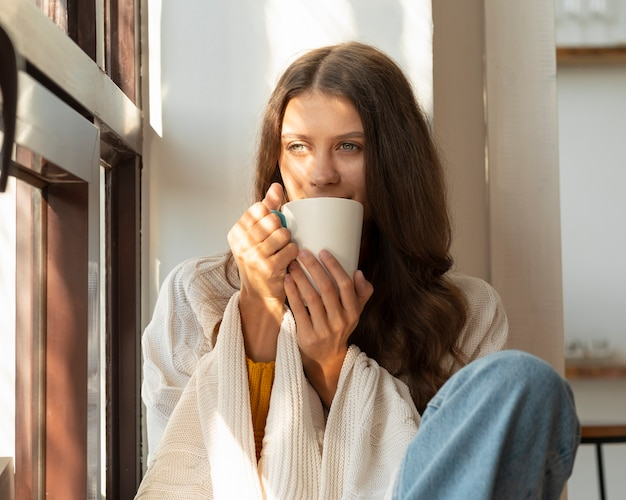 Mulher tomando bebida quente e curtindo a manhã, sentada na janela e sonhando