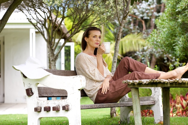 Mulher tomando café ao ar livre no jardim