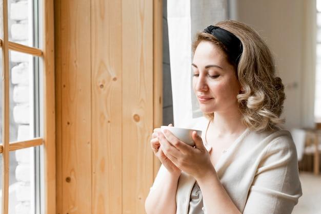 Mulher tomando café ao lado de sua janela