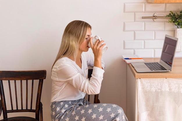Mulher tomando café com vista lateral