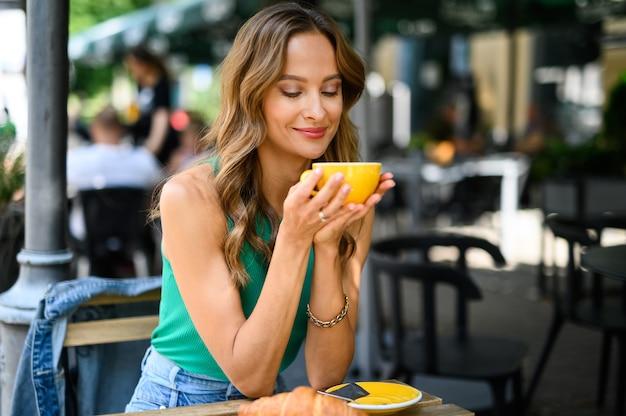 Mulher tomando café da manhã ao ar livre no centro da cidade