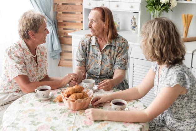 Mulher tomando café da manhã com a mãe e a avó em casa