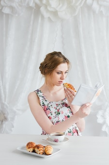 Mulher tomando café da manhã com chá e croissants frescos caseiros