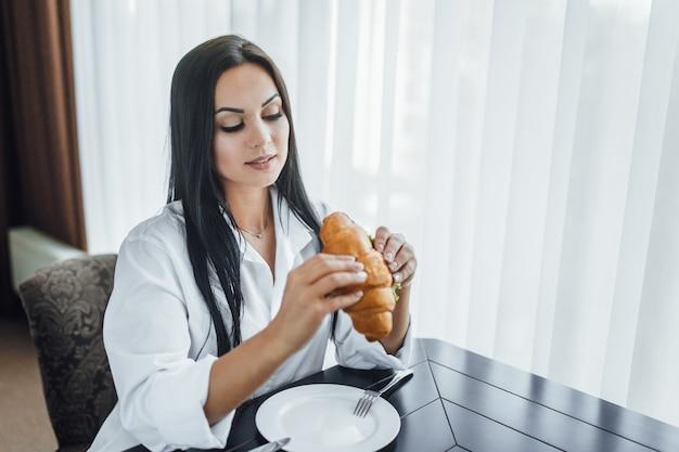 Mulher tomando café da manhã com croissant pela manhã