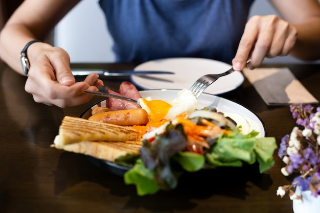 Mulher tomando café da manhã com ovos fritos, salsichas, vegetais e torradas.